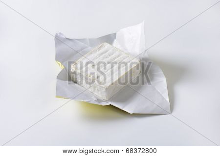 block of cow's milk cheese in a paper wrapper