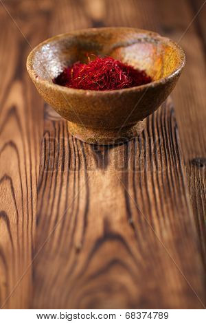 saffron spice in earthenware bowl on old textured wooden background, closeup