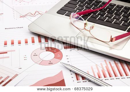 Laptop And Glasses With Red Business Charts, Graphs, Research And Reports