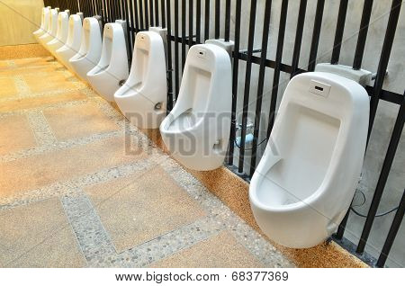 Line Of White Urinals In Public Toilet