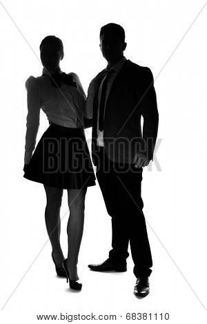 Silhouettes on white of a stylish couple standing side by side looking at the camera, woman in a miniskirt and high heels and man in a suit