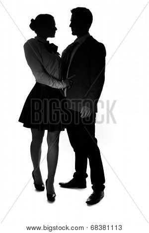 Loving young couple in silhouette standing with their arms around each other looking into each others eyes, on white