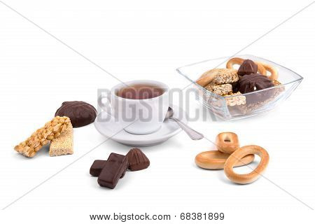 White Cup Of Tea And A Selection Of Sweets On A White Background