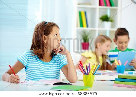 Portrait of pensive girl drawing at workplace with her schoolmates on background