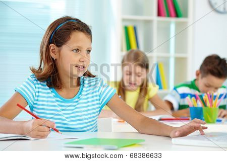 Portrait of cute girl working at workplace with her schoolmates on background