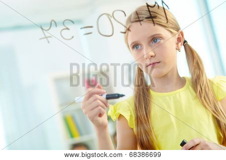 Portrait of lovely girl doing sums on transparent board at lesson