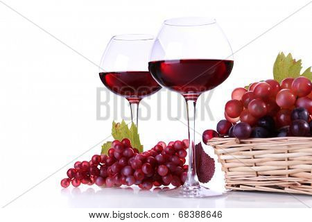 Wineglasses with red wine and  grape in wicker basket isolated on white