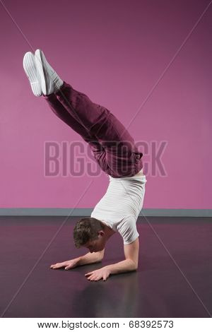 Cool break dancer doing handstand in the dance studio