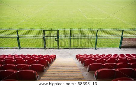 Red bleachers looking down on football pitch on a clear day