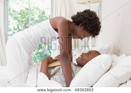 Intimate couple messing about in the morning on bed at home in the bedroom