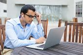 picture of indian blue  - Closeup portrait young man in blue shirt and black glasses listening to headphones browsing digital computer laptop isolated background of sunny outdoor gray building waterfall with brown chairs - JPG