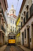 stock photo of tram  - Narrow street in old Lisbon downtown with typical yellow tram - JPG