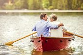 foto of boat  - Senior couple paddling on boat on mountain tarn - JPG