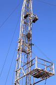 picture of derrick  - Derrick of Small Workover Rig on Sunny Day - JPG