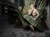 picture of implied nudity  - Handsome naked man covered by a palm frond - JPG