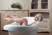 stock photo of nipple  - Sexual young blonde nude woman posing with bare breast seductively in the bath - JPG