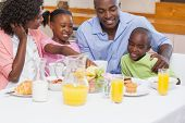 stock photo of arms race  - Happy family having breakfast together in the morning at home in the kitchen - JPG