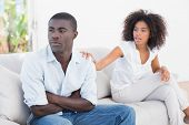 picture of argument  - Attractive couple having an argument on couch at home in the living room - JPG