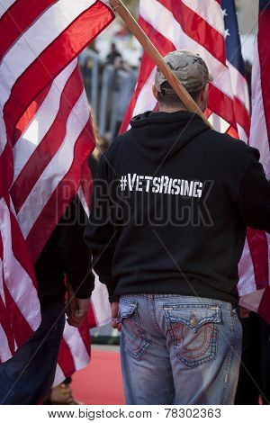 NEW YORK - NOV 11, 2014: A US vet wearing a hoodie that says #VetsRising carries the American Flag in the 2014 America's Parade held on Veterans Day in New York City on November 11, 2014.