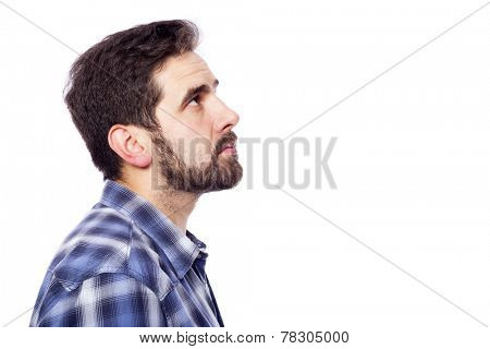 Side view of a pensive casual man looking up, isolated over white background