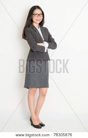 Full body Asian business woman standing on plain background.