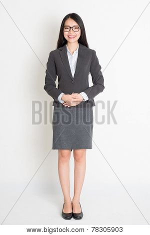 Full body smiling Asian business woman standing on plain background.
