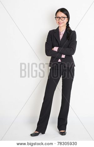 Full body Asian business woman smiling and standing on plain background.