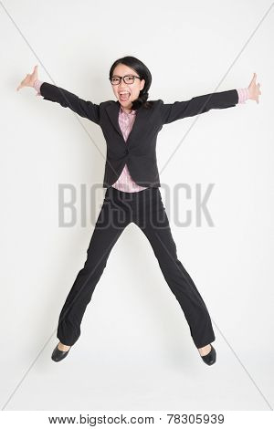 Full length of Asian successful business woman leaping high in the air, on plain background.