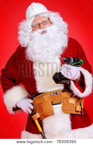 Portrait of Santa Claus - builder in helmet builder holding construction tools over red background.