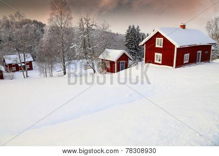 old cottages set in a snowy winter landscape, Sweden