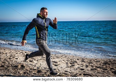 Running man jogging on beach.