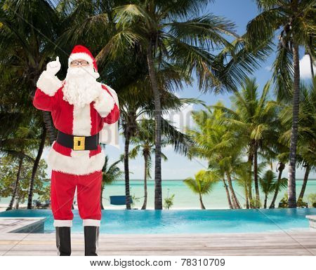 christmas, holidays, gesture, travel and people concept - man in costume of santa claus with bag pointing finger up over tropical beach and swimming pool background