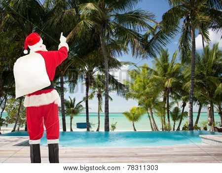 christmas, holidays, travel and people concept - man in costume of santa claus with bag pointing finger from back over tropical beach and swimming pool background