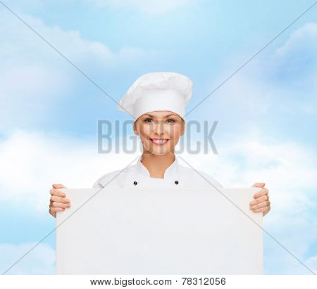 cooking, advertisement and people concept - smiling female chef, cook or baker with white blank board over blue cloudy sky background