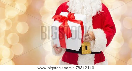 christmas, holidays and people concept - close up of santa claus with gift box over beige lights background