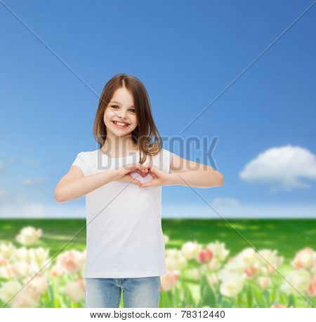 advertising, childhood, nature, gesture and people concept - smiling girl in white t-shirt making heart-shape gesture over field background