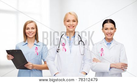 healthcare and medicine concept - female doctors with pink breast cancer awareness ribbon