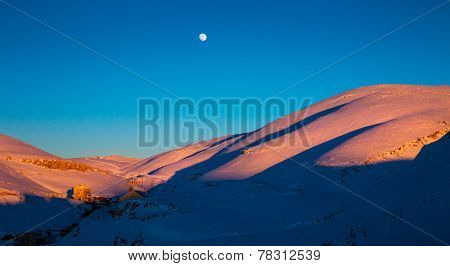 Beautiful winter landscape, high majestic mountains covered with white snow in bright sunset light, small moon in clear blue sky, beauty of wintertime nature