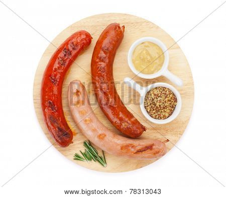 Various grilled sausages with condiments on cutting board. Isolated on white background