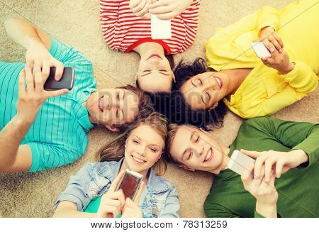 education, technology and happiness concept - group of young smiling people lying down on floor in circle with smartphones