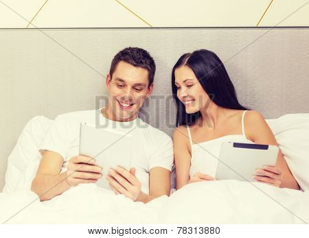 hotel, travel, relationships, technology, intermet and happiness concept - smiling couple in bed with tablet computers
