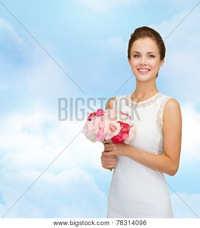 people, wedding, holidays and celebration concept - smiling bride or bridesmaid in white dress with bouquet of flowers over blue cloudy sky background