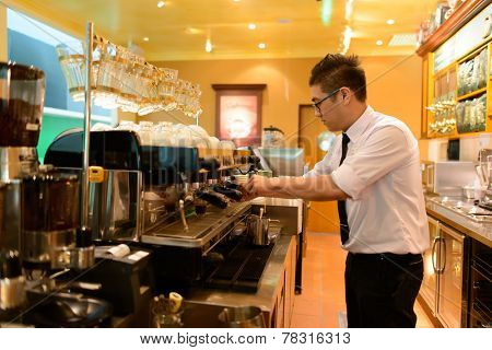 KUALA-LUMPUR - MAY 06: barman prepare coffee in airport cafe on May 06, 2014 in Kuala-Lumpur, Malaysia. Kuala Lumpur International Airport is one of the major airports of South East Asia.