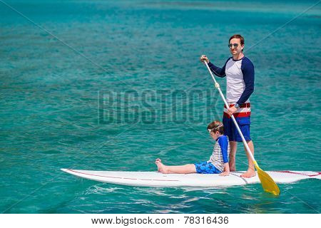 Father and son paddling on stand up board having fun during summer beach vacation
