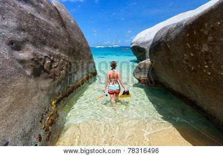 Young woman with snorkeling equipment at tropical beach among granite boulders at Virgin Gorda, British Virgin Islands, Caribbean