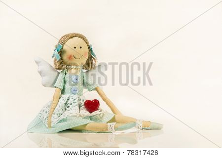 Angel figurine holding a red heart in his hands - isolated object for a greeting card.