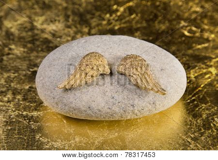 Stone with golden angel wings: greeting card for die, death, communion or christening.