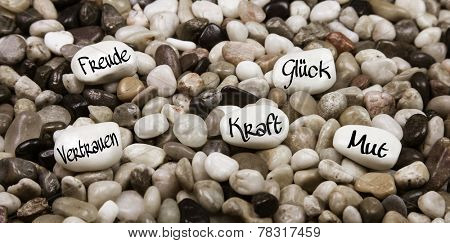 Pebble stones with german text for luck, happiness, love, confidence, courage and power. Idea for a greeting card.