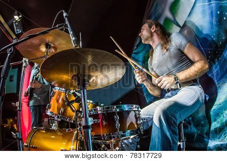 Drummer (focus on the drum and microphone) playing on drum set on stage. Warning - authentic shooting with high iso in challenging lighting conditions. A little bit grain and blurred motion effects.