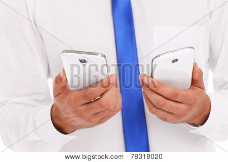 A midsection of a businessman with two smarphones